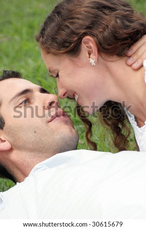 beautiful loving couple laying in grass with faces close together looking into each others eyes about to kiss - stock photo