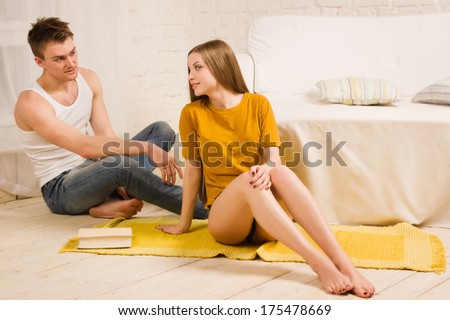 Beautiful loving couple reading a book on the floor