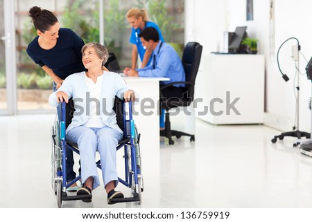 beautiful loving daughter taking senior mother visiting doctor - stock photo