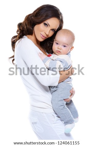 Beautiful loving mother holding her adorable little baby clasped in her arms standing sideways looking at the camera isolated on white - stock photo