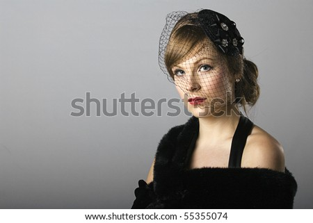 beautiful low key dramatic image of a woman in a veil and 1930s dress