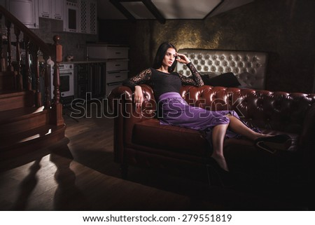 beautiful luxurious brunette woman sitting on a leather vintage sofa - stock photo