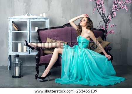 Beautiful luxurious woman on a vintage couch - stock photo