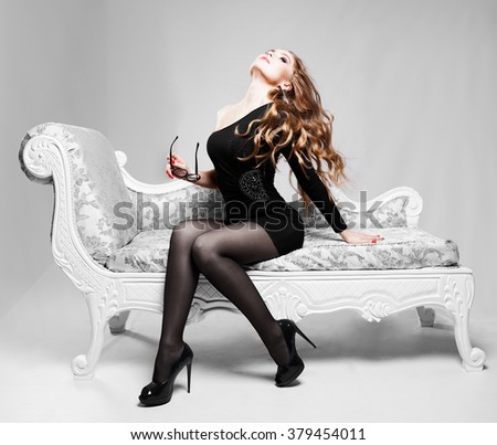 beautiful luxurious woman sitting on a vintage couch - stock photo