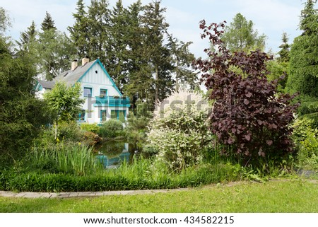 Beautiful luxury house situated in in spring garden, with conifers, trees and flower. Springtime in private beautiful garden.