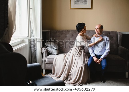 Beautiful luxury newlyweds sitting on the sofa in the room