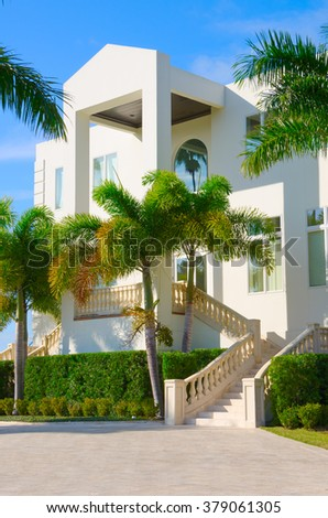 Beautiful luxury residential home with front stairways and lush green palm trees against a blue morning sky - stock photo
