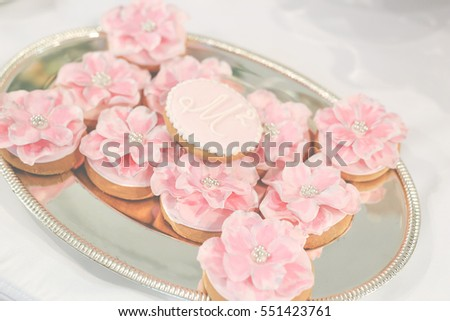 Beautiful luxury sweet candy bar set on the table at the wedding ceremony in restaurant. Flower rose bouquet and tasty desserts on the table. Confectionery business concept.