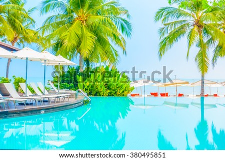 Beautiful luxury swimming pool in hotel pool resort with umbrella beach and chair - Vintage Filter and Boost up color Processing - stock photo