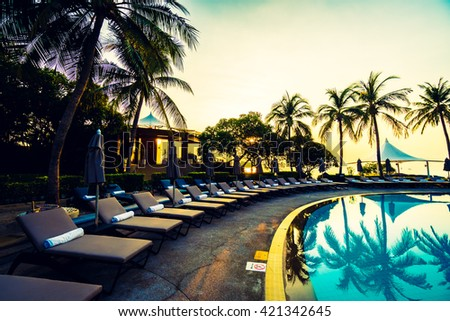 Beautiful luxury umbrella and chair and coconut palm tree around outdoor swimming pool in hotel resort at sunrise time - Vintage filter and boost up color Processing - stock photo