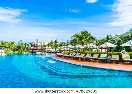 Beautiful Luxury Umbrella And Chair Around Outdoor Swimming Pool In Hotel  And Resort With Coconut Palm
