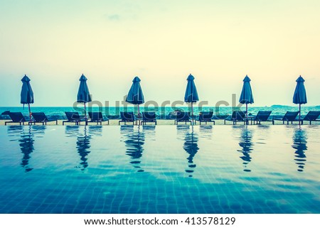 Beautiful luxury umbrella and chair around outdoor swimming pool in hotel resort neary sea and beach - Vintage Filter - stock photo