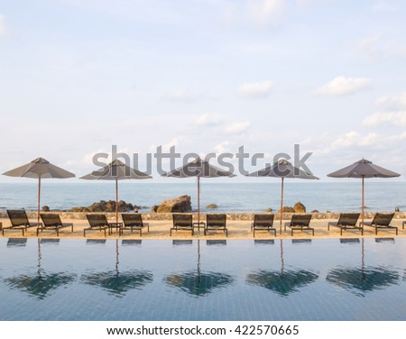 Beautiful luxury umbrella and chair around outdoor swimming pool in hotel resort neary sea and beach - Boost up color Processing style - stock photo