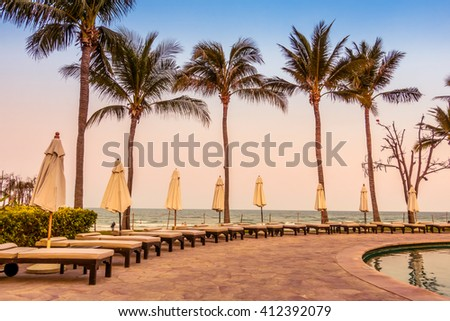 Beautiful luxury umbrella and chair around swimming pool in hotel pool resort with coconut palm tree at sunset times - Vintage Filter and Boost up color Processing