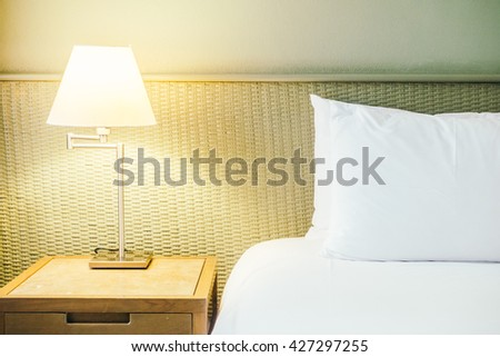 Beautiful luxury white pillow on bed with table light lamp beside bed decoration in bedroom interior - Vintage light Filter