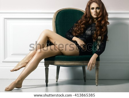 Beautiful luxury woman model posing in black lacy dress in rertro chair. Beautiful portrait in interior. Fashion evening curly hairstyle, long hair, slim voluptuous body shapes, long legs.  - stock photo