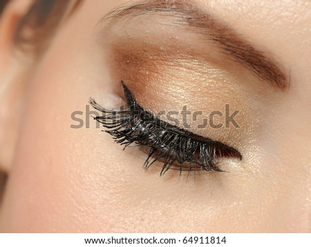 Beautiful macro shot of eye with long lashes and make-up in brown tones - stock photo
