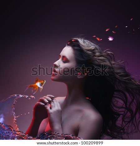 Beautiful magic girl talking with golden fish that made water splashes - stock photo