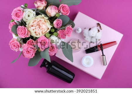 Beautiful make up bag with cosmetics and flowers on pink background