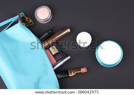Beautiful make up bag with cosmetics on black background - stock photo