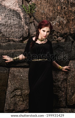 Beautiful makeup girl wearing black tunic and an antique jewels, rocky wall on background - stock photo