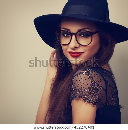 Beautiful makeup woman in fashion black hat and eyeglasses looking with smiling. Toned closeup portrait