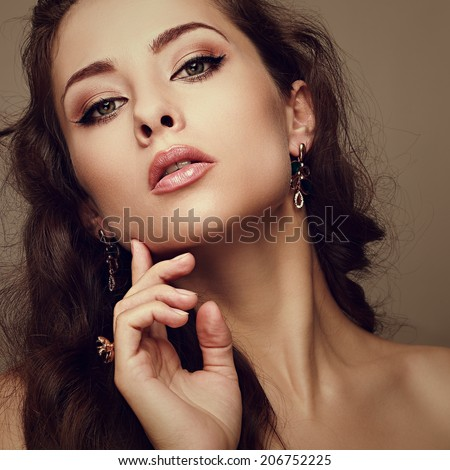 Beautiful makeup woman looking with sexy look and touching fingers face. Closeup art portrait - stock photo
