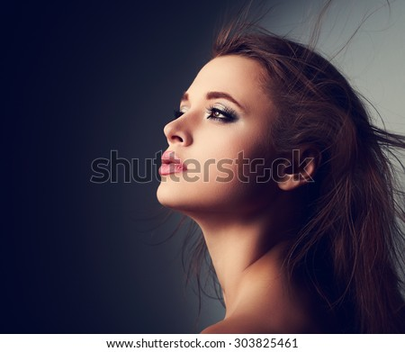 Beautiful makeup woman profile with long hair looking up with hope on light on dark background - stock photo
