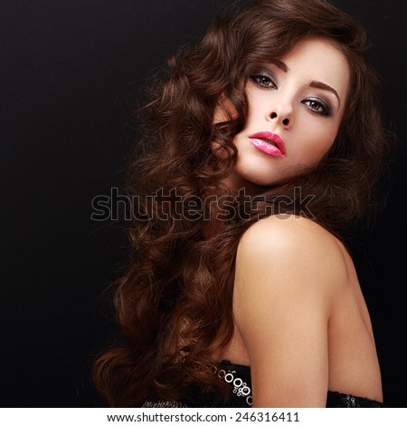 Beautiful makeup woman with curly hair looking on black. Closeup portrait