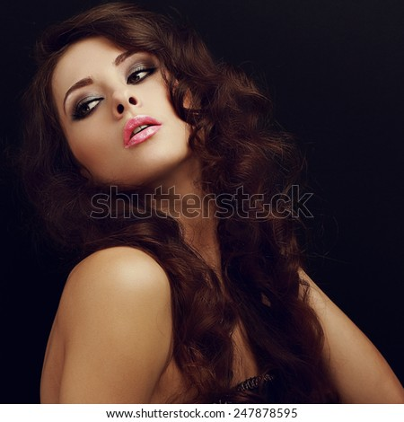 Beautiful makeup woman with long curly hair and pink lips looking back on black background. Closeup portrait - stock photo