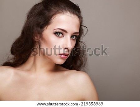Beautiful makeup woman with long lashes and curly hair on gray background