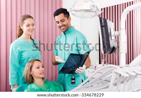 Beautiful male dentist and patient looking x-ray scan - stock photo
