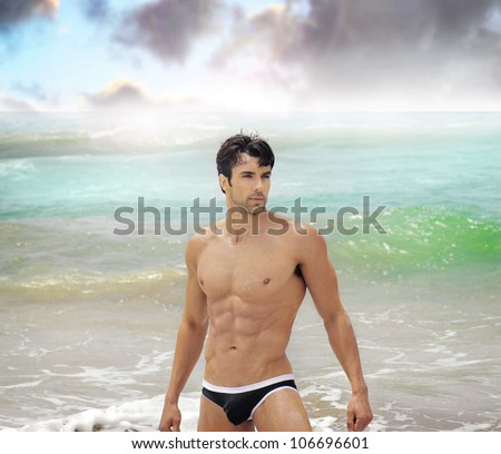 Beautiful male model in sexy swimwear in the ocean at beach