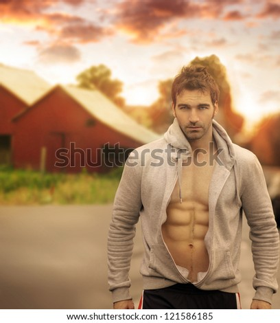 Beautiful male model with great body in romantic rustic outdoor setting with red barn in background and moody sky above - stock photo