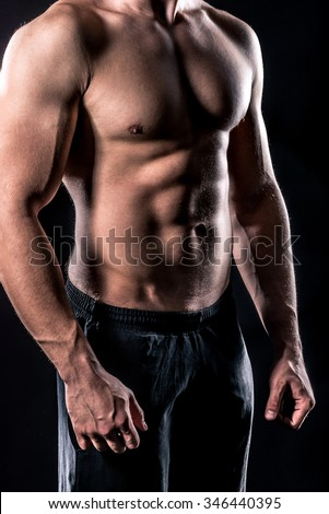 beautiful male torso isolated over black background