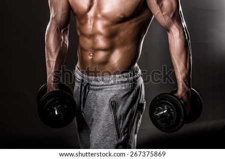 Beautiful male torso with weights - stock photo