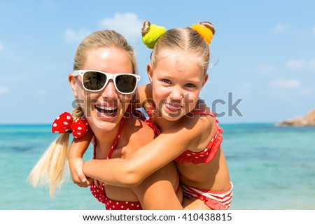 Beautiful mammy sunglasses with cute little daughter on her back. Two in red bikini. Woman and little lady smile and looking to camera. Happy family on the sea shore. Happy mothers day.