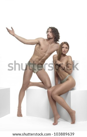 beautiful man and woman Adam and Eve, posing on a white background with white cubes - stock photo