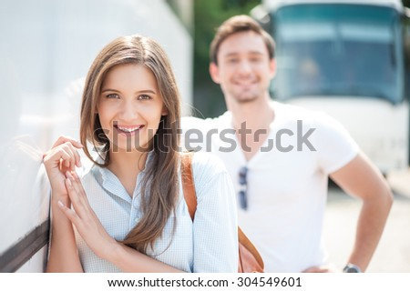 Beautiful man and woman are stranding near a bus. They are waiting for bus departure. They are smiling. Focus on woman