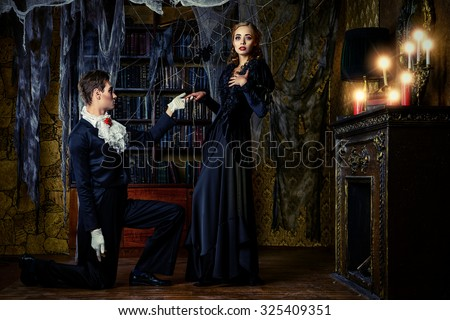 Beautiful man and woman vampires dressed in medieval clothing stand in a room of the old abandoned castle. Halloween.  - stock photo
