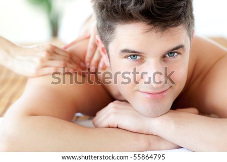 Beautiful man enjoying a back massage in a Spa center - stock photo