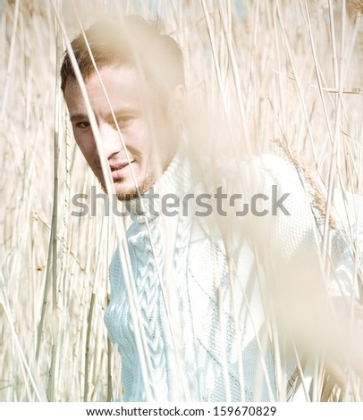Beautiful man in the jungles of reeds - stock photo