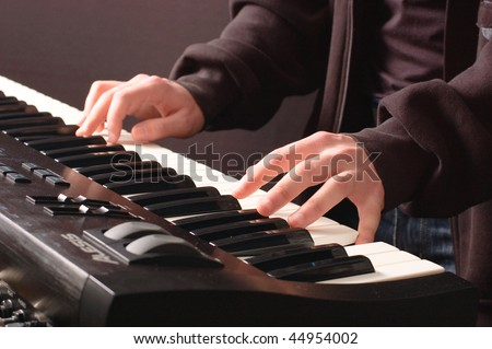 Beautiful man's hands on the keys of synthesizer - stock photo