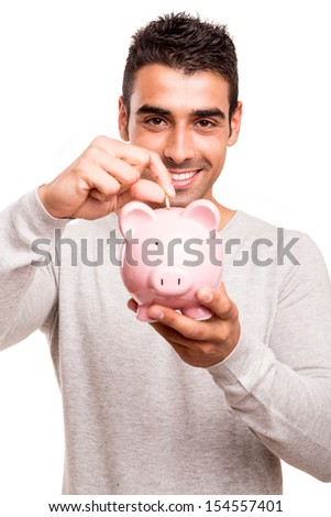 Beautiful man saving money to a piggy bank
