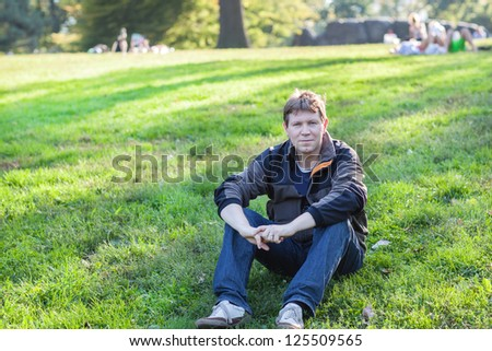 Beautiful man sitting on grass in spring Central park New York