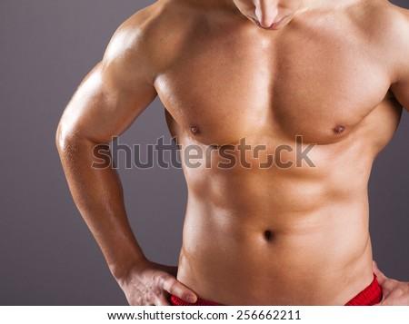 Beautiful man torso on grey background - stock photo