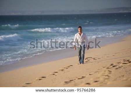 beautiful man walking alone in desert beach - stock photo
