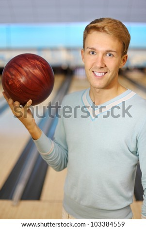 Beautiful man wearing in blue pulover holds red ball in bowling club; shallow depth of field - stock photo
