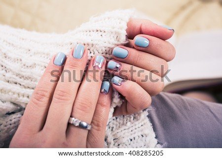 beautiful manicure. Gel polish coating in blue, embossing. - stock photo