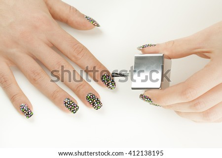Beautiful manicure process. Nail polish being applied to hand, polish is a blue color